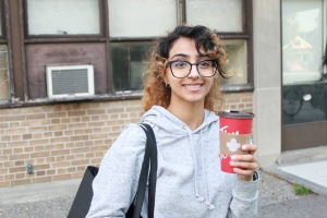 Photo of Khyati with a coffee in hand.